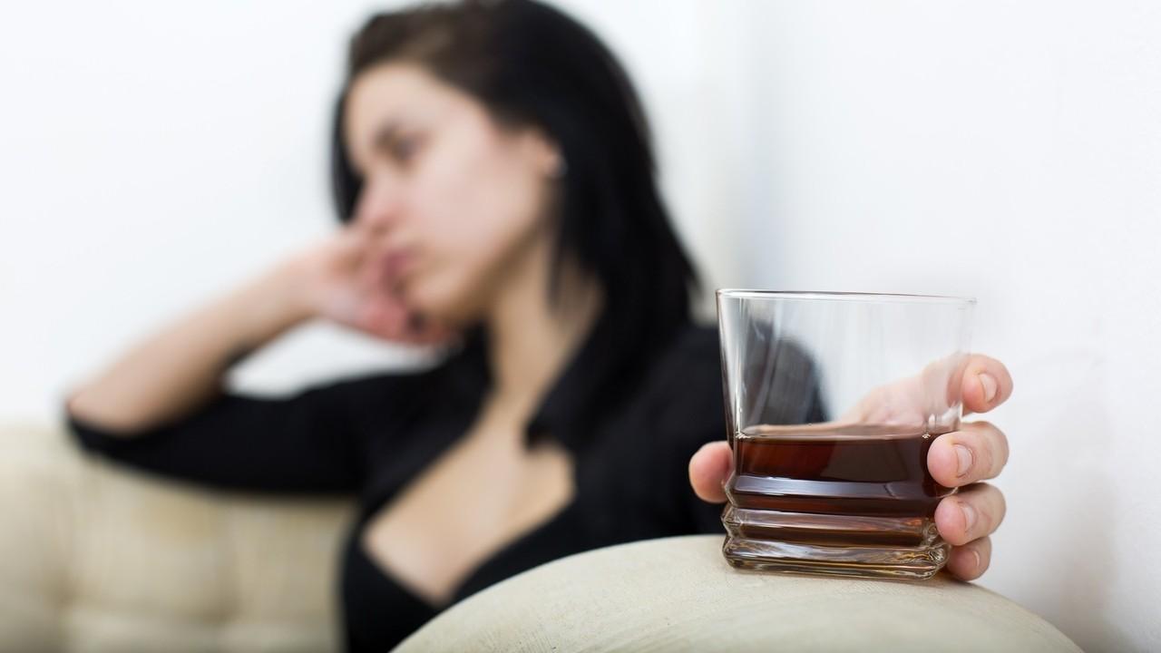 Sad girl holding glass of scotch