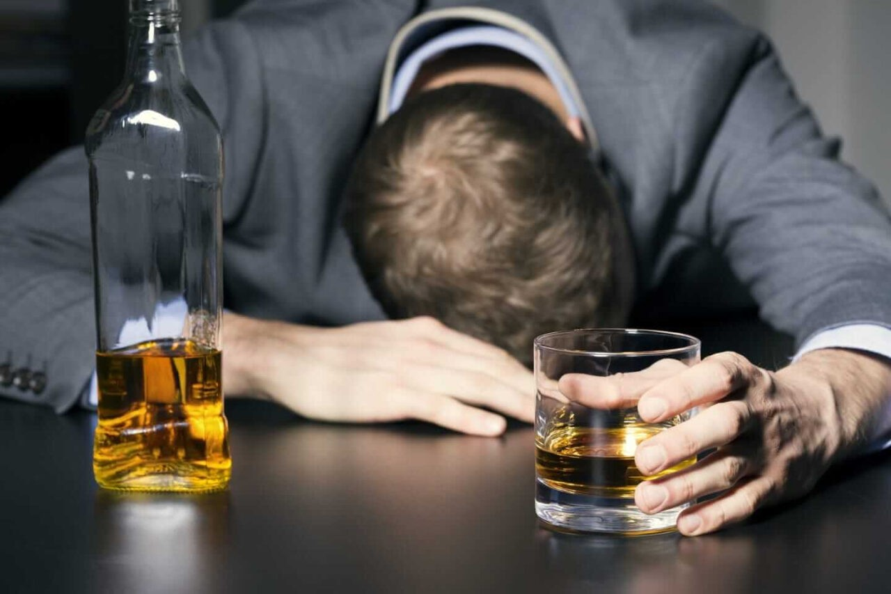 Drunk-businessman-holding-a-glass-of-whiskey-1